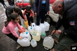 FILE - People fill plastic containers with water from a tap in Damascus, Syria, Jan. 16, 2017.