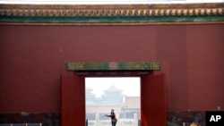 A visitor wearing a face mask to protect against the new coronavirus walks through the Forbidden City in Beijing, May 1, 2020. The Forbidden City reopened on Friday, China's May Day holiday, to limited visitors.