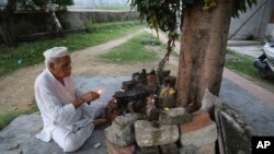 Kashmiri Hindu man, Sham Lal, 63 performs evening prayers at the Muthi migrant camp in Jammu, India, Aug. 29, 2019. Tens of thousands of Kashmiri Hindus fled the restive region nearly 30 years ago.