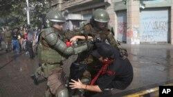 Seorang polisi menahan seorang pengunjuk rasa anti-pemerintah di Santiago, Chile, Sabtu, 26 Oktober 2019.