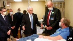 Vice President Mike Pence, center, visits Dennis Nelson, a patient who survived the coronavirus and was going to give blood, during a tour of the Mayo Clinic Tuesday, April 28, 2020.