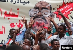 FILE - Protesters shout slogans by a banner depicting former Sudanese President Omar al-Bashir, in front of the Defense Ministry in Khartoum, Sudan, April 19, 2019.