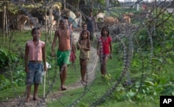 Indian children stand by a fence on the India-Bangladesh border at Jhalchar, in the northeastern Indian state of Assam.