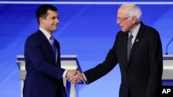 Democratic presidential candidates former South Bend Mayor Pete Buttigieg and Sen. Bernie Sanders, I-Vt., shake hands on stage Friday, Feb. 7, 2020, before the start of a Democratic presidential primary debate hosted by ABC News, Apple News, and…