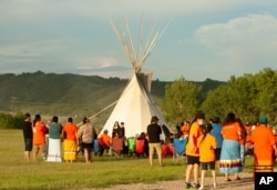 A vigil takes place where ground-penetrating radar recorded hits of what are believed to be 751 unmarked graves near the grounds of the former Marieval Indian Residential School on the Cowessess First Nation, Saskatchewan, June 26, 2021.