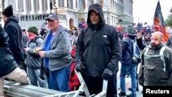 Un hombre (centro con abrigo negro) identificado por los fiscales federales de Estado Unidos como Shane Jason Woods de Auburn, Illinois. Captura de fotograma de un video filmado durante el asalto del 6 de enero de 2021 al Capitolio.