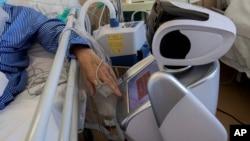2020年4月8日意大利瓦雷泽市接受治疗的冠状病毒患者与机器人互动。