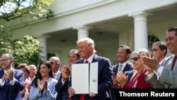 El presidente Donald Trump posa con el decreto sobre la Iniciativa para la Prosperidad Hispana de la Casa Blanca instantes después de firmar el documento.