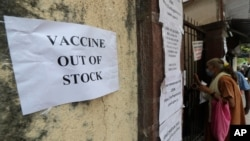 FILE - A note about the non-availability of COVID-19 vaccine is seen pasted on a wall of a vaccination site in Mumbai, India, April 8, 2021.