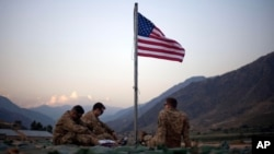 FILE - In this Sept. 11, 2011 photo, US soldiers sit beneath an American flag just raised to commemorate the tenth anniversary of the 9/11 attacks at Forward Operating Base Bostick in Kunar province, Afghanistan.
