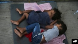 FILE - Migrant children sleep on a mattress on the floor of the AMAR migrant shelter in Nuevo Laredo, Mexico, July 17, 2019. The ACLU said Thursday that more than 5,400 children were separated from their parents by the Trump administration.