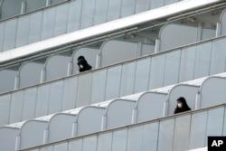 Masked passengers stand outside on the balcony of the cruise ship Diamond Princess anchored at Yokohama Port in Yokohama, near Tokyo, Feb. 7, 2020.