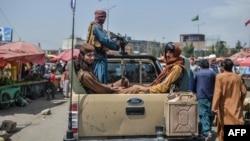 Talibanski borci u vozilu prolaze pijačnom oblašću, između tezgi i lokalnih kupaca, u Kabulu, Afganistan, 17. avgusta 2021.
