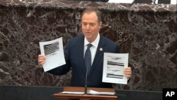 In this image from video, House impeachment manager Rep. Adam Schiff holds redacted documents as he speaks during the impeachment trial of President Donald Trump, in the Senate at the Capitol in Washington, Jan. 22, 2020. (U.S. Senate TV via AP)