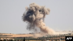 Smoke billows during pro-regime bombardments in the area of Maar Hitat in Syria's northern Idlib province, Aug. 20, 2019.