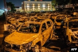 FILE - The carcasses of the cars burned by protesters the previous night during a demonstration against the shooting of Jacob Blake are seen on a used-cars lot in Kenosha, Wisconsin, Aug. 26, 2020.