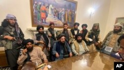 Los combatientes talibanes toman el control del palacio presidencial afgano después de que el presidente afgano Ashraf Ghani huyera del país, en Kabul, Afganistán, el domingo 15 de agosto de 2021 (AP Photo / Zabi Karimi).