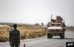 FILE - A fighter from the Syrian Democratic Forces stands guard as a convoy of U.S. military vehicles drives on a road after U.S. forces pulled out of their base in the northern Syrian town of Tal Tamr, Oct. 20, 2019.