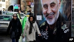 تہران میں دو خواتین امریکی ڈرون حملے میں ہلاک ہونے والے القدس فورس کے جنرل قاسم سلیمانی کے پوسٹر کے پاس سے گزر رہی ہیں۔ اس کے جواب میں ایران نے عراق میں امریکی فوجی اڈوں کو نشانہ بنایا تھا۔