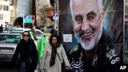 Women walk past a banner of Iranian Revolutionary Guard Gen. Qassem Soleimani, who was killed in Iraq in a U.S. drone attack Friday, in Tajrish square in northern Tehran, Iran, Jan. 9, 2020.