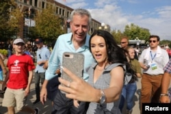 Democratic U.S. presidential candidate and New York City Mayor Bill de Blasio takes a photo with a fairgoer at the Iowa State Fair in Des Moines, Iowa, Aug. 11, 2019.