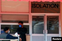 Men wear protective mask as a preventive measure against coronavirus, as they stand outside the Isolation ward at the Pakistan Institute of Medial Sciences (PIMS) in Islamabad, Pakistan, March 15, 2020.