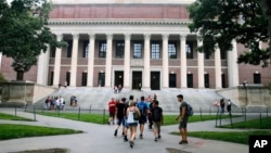 FILE - Students walk near the Widener Library at Harvard University in Cambridge, Massachusetts, Aug. 13, 2019.
