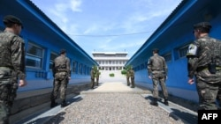 韩国军人(前)与朝鲜军人(后)在板门店停战村执勤