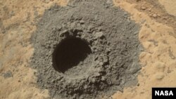 "NASA's Mars rover, Curiosity, completed a shallow ""mini drill"" activity as part of an evaluatiion of a rock target called ""Windjana"" for possible full-depth drilling to collect powdered sample material from the rock's interior, April 29, 2014."