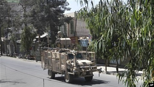 A NATO military vehicle crosses the empty street after gunmen launched an attack on the compound of the governor of Kandahar province  in Kandahar, south of Kabul, Afghanistan, May 7, 2011
