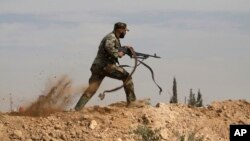 FILE - A Shi'ite fighter clashes with members of the Sunni-dominated Free Syrian Army rebel in the town of Hatita, in the countryside of Damascus, Syria, Nov. 22, 2013.
