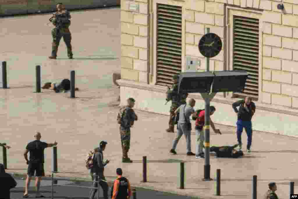 French police point a gun at a man on the ground (C) as a stabbed woman lies (L) while soldiers secure the area following an attack at the Saint-Charles main train station in the French Mediterranean city of Marseille. A suspected Islamist man killed two women at the main train station in Marseille before being shot dead by soldiers on patrol, local officials and police said.