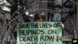 A member of Migrante International, a Filipino migrant organization, displays a placard demanding legal assistance for her relatives during a protest outside the presidential palace in Manila, February 21, 2011.