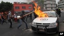 Người biểu tình đốt xe cảnh sát gần sân bay ở thành phố Mexico, ngày 20/11/2014.