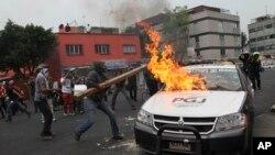 Para pemrotes membakar mobil polisi saat berunjuk rasa di Mexico City, Kamis (20/11).
