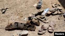 FILE - The shoes of men who were dug up from a mass grave are seen outside the town of Sulaiman Pek in northern Iraq September 5, 2014. Many such graves are appearing in Iraq.