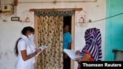 Zdravstveni radnici od vrata do vrata prikupljaju podatke za anketu u predgrađu Ahmedabada u Indiji, 14. decembra 2020.