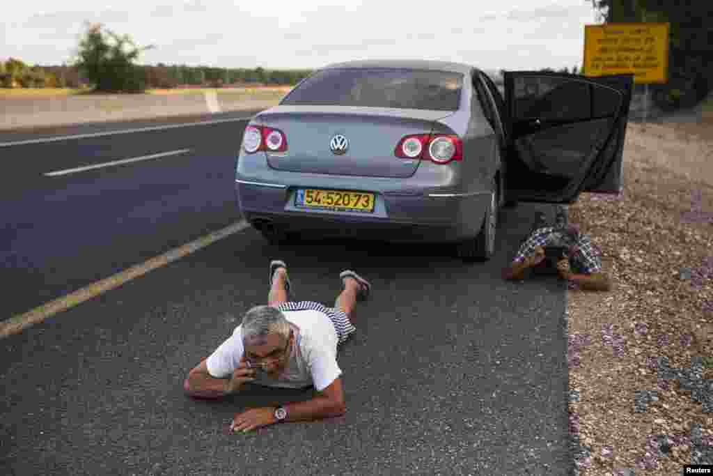 Israelis take cover by the side of a road as a siren sounds a warning of incoming rockets, outside the northern Gaza Strip, July 15, 2014.