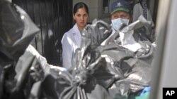 Nhân viên pháp y xử lý các túi chứa thi thể bị chặt đầu và chân tay của các nạn nhân tại nhà ở Guadalajara, ngày 9/5/2012