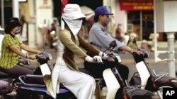 Người dân đeo khẩu trang để chống ô nhiễm khi lái xe trên đường phố ở TP HCM.