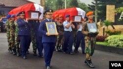 Dua jenazah korban kecelakaan pesawat T50i Golden Eagle; Letkol Marda Sarjono (kiri) dan Kapten Dwi Cahyadi (kanan) diberi penghormatan dan diserahkan kepada keluarga (dari TNI AU) di Base Ops Lanud Adisucipto, Minggu (20/12) petang (VOA/Munarsih).