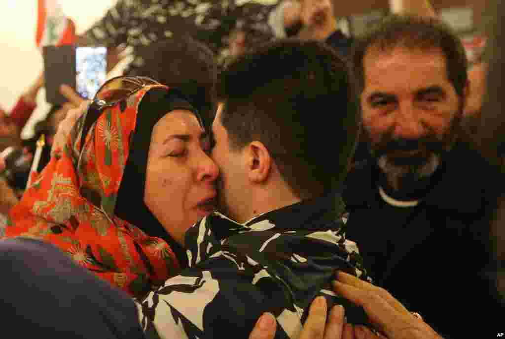 A Lebanese policeman, center, who was kidnapped by Nusra Front, hugs his mother, left, upon his arrival at the government palace, in Beirut. Syria's al-Qaida branch released a group of Lebanese troops held captive for over a year as part of a Qatar-brokered swap that involved Lebanon setting free at least 11 prisoners wanted by the militants, including a former wife of the Islamic State leader Abu Bakr al-Baghdadi.