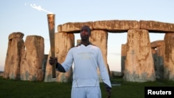 Former U.S. Olympic athlete Michael Johnson holds the Olympic Torch at Stonehenge, a World Heritage site, in Salisbury, southern England, July 12, 2012.