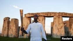Former U.S. Olympic athlete Michael Johnson holds the Olympic Torch at Stonehenge, a World Heritage site, in Salisbury, southern England July 12, 2012.