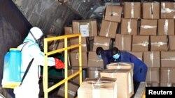 2020年4月5日身穿防护服的医疗成员为到达南苏朱巴国际机场货物消毒