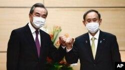 日本首相菅義偉在東京會晤到訪的中國外長王毅。(2020年11月25日)