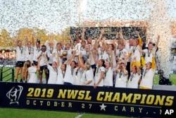 North Carolina Courage merayakan kemenangan mereka atas Chicago Red Stars dengan berfoto bersama trofi kejuaraan seusai pertandingan sepak bola kejuaraan NWSL di Cary, N.C., 27 Oktober 2019.