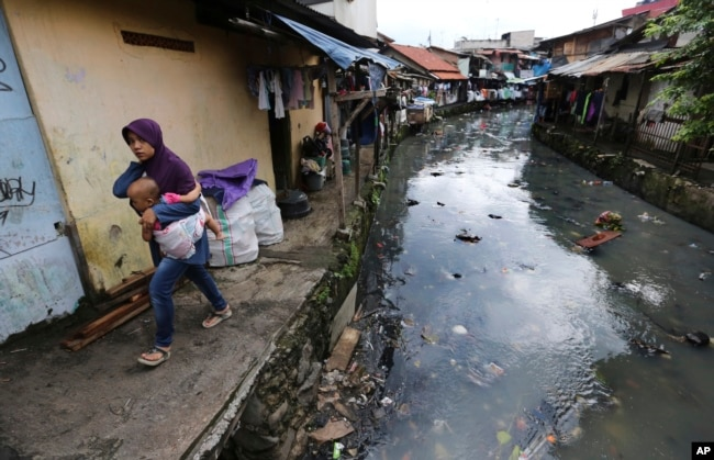 A woman carrying a child walks along a garbage-strewn river at a slum in Jakarta, Indonesia, April 3, 2017. Most of Jakarta's waterways are polluted, contributing not only to a lack of clean water, but also making flooding more likely during the rainy season.