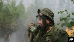 Maxim Yefremov, member of volunteers crew adjusts his gas mask as he mops up spot fires at Gorny Ulus area west of Yakutsk, Russia, July 22, 2021.