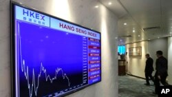 A screen displays the Hong Kong share index at the Hong Kong Stock Exchange on Oct. 4, 2021. Shares in troubled real estate developer China Evergrande Group and its property management unit Evergrande Property Services were suspended from trading Monday i